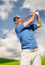 Golfer shooting a golf ball and blue sky Stock Image