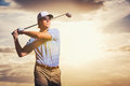 Golfer at sunset man swinging golf club with dramatic sky Royalty Free Stock Photo