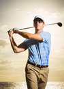 Golfer at sunset man swinging golf club with dramatic sky Royalty Free Stock Image