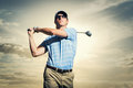 Golfer at sunset man swinging golf club with dramatic sky Royalty Free Stock Photos