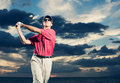 Golfer at sunset man swinging golf club with dramatic sky backdrop Stock Photography