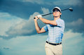 Golfer swinging golf club at sunset man with dramatic blue sky Royalty Free Stock Photos