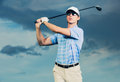 Golfer swinging golf club at sunset man with dramatic blue sky Stock Photo