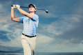 Golfer swinging golf club at sunset man with dramatic blue sky Royalty Free Stock Photography