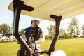 Golfer taking clubs from a bag in a golf cart Royalty Free Stock Photo