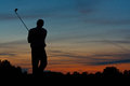 Golfer teeing off at dusk silhouette of a lone finishing a game of golf Stock Photos