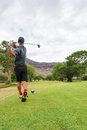 Golfer tees off from tee box to fairway Royalty Free Stock Photo