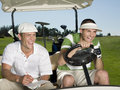 Golfers sitting in golf cart cheerful young male at course Royalty Free Stock Photo