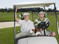 Golfers sitting in golf cart two young male Royalty Free Stock Images