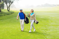 Golfing couple walking on the putting green Royalty Free Stock Photo