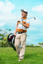After golfing full length image of a mature golf player with a sports rucksack walking on the lawn Royalty Free Stock Photo