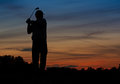 Golfing silhouette of a golfer teeing off early at dawn Stock Photos
