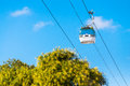 Gondola lift a over trees aerial cable car supported and propelled by cables from above Stock Photo