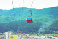 Gondola ropeway above city with mountains in the back Royalty Free Stock Image