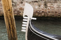 Gondola s prow detail of a next a pylon and a wall in a venetian canal Stock Photo