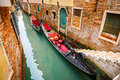 Gondolas on canal in venice narrow italy Stock Photos