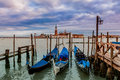 Gondolas on grand canal in venice italy tied as san giorgio maggiore church background under cloudy sky at evening Royalty Free Stock Photo