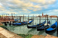 Gondolas moored in row on grand canal in venice a at wooden pier against background of san giorgio maggiore church italy Royalty Free Stock Photos