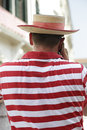 Gondolier back view of a talking on the telephone he is a wearing a the traditional white and red striped shirt and a straw hat Royalty Free Stock Images