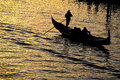 Gondolier black silhouette of and gondola on sunset color water surface of canal in venice Stock Image