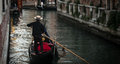 Gondolier on the canal back and hat a Stock Image
