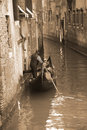 Gondolier carrying tourists in Venice, sepia tone Royalty Free Stock Photo