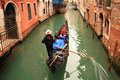Gondolier making tour in lovely canal of venice Stock Photo