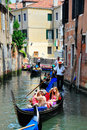 Gondolier navigating a gondola through canal Royalty Free Stock Photography