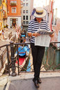 Gondolier in venice italy july reading a newspaper on a small bridge waiting for tourists to come Royalty Free Stock Photo