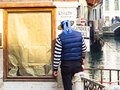 Gondolier in Venice offering the transport service Royalty Free Stock Photo