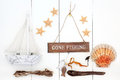 Gone fishing abstract nautical background with sign driftwood starfish and scallop shells seaweed and decorative wooden boat over Stock Photo