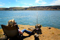 Gone fishing lady for sturgeon on the columbia river in eastern washington with view of territory under clear blue skies copy Royalty Free Stock Photography