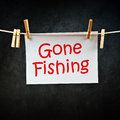 Gone fishing note printed on paper attached to a rope with clothes pins Royalty Free Stock Photo