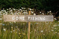 Gone fishing sign among flowers on a pole summer Royalty Free Stock Photography