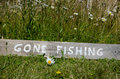 Gone fishing sign wooden at a lawn with daisies Stock Image