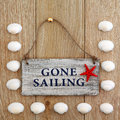Gone sailing sea shell abstract and sign over old oak background Stock Image