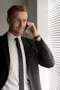 Good business news confident young businessman talking at mobil mobile phone and looking away Stock Photo