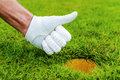 Good job close up of male hand in golf glove gesturing thumb up near the hole in gold course Stock Images