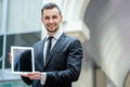 Good job successful businessman in formal wear holding a tablet his hands the business center and shows the camera Royalty Free Stock Photo