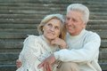 Good looking elderly couple at wall standing Stock Photo