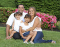 Good looking family sitting on grass portrait Royalty Free Stock Photos