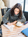 Good looking girl writing something on a notebook with a cup of cappuccino Royalty Free Stock Photo