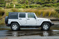 Good looking off road car silver new unmarked and modern sport utility vehicle parked on wet sand outdoors Stock Photography