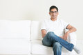 Good looking young indian guy sitting on sofa and smiling lifestyle asian man at home handsome male model Royalty Free Stock Image
