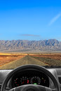 Good luck wheel and dashboard of the car going on the desert road to far mountains Stock Photography