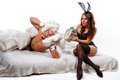 Good morning close up of couple lying in bed woman rabbit holds alarm clock near the ear of man Stock Photography