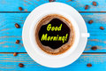 Good Morning - inspiration wishes on coffee cup at blue wooden background. Top view Royalty Free Stock Photo