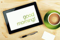 Good morning message on tablet computer screen office table Royalty Free Stock Image