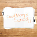 Good morning sunday on paper and brown wood plank background Stock Images