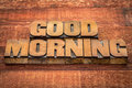 Good morning typography text in vintage letterpress wood type against rustic barn wood table Royalty Free Stock Photos